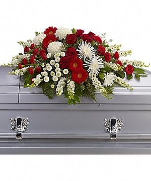 Red and white floral casket spray accented with greenery.