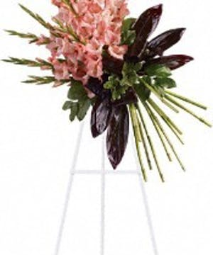 Coral gladioli and greenery displayed on an easel.