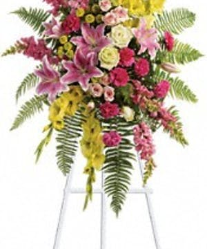 Sympathy spray of bright yellow and pink tropical flowers.