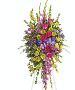 Sympathy spray of purple, lavender, pink and yellow flowers.