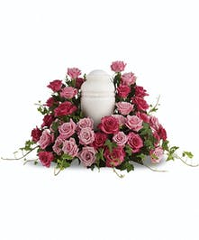 Sympathy arrangement of light and hot pink roses to surround an urn.