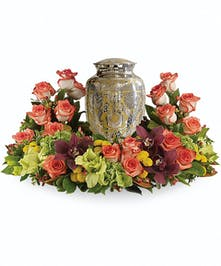 Sympathy arrangement of orange, green, brown and yellow flowers to surround an urn.