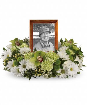 Sympathy arrangement of white and green flowers to surround an urn or photograph.