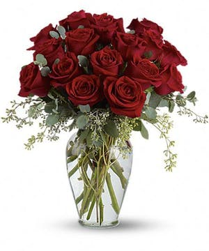 Sixteen red roses in a clear glass vase.