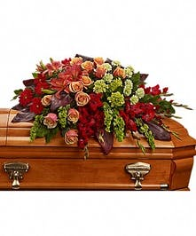 Casket spray of orange roses and lilies.
