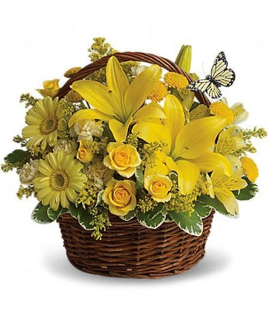 Bright yellow flowers in a basket with butterfly decoration.