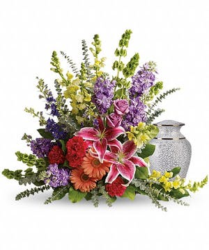 Sympathy arrangement of lilies, roses and snapdragons to surround an urn.