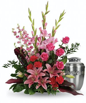 Sympathy arrangement of hot pink and pink flowers to surround an urn.