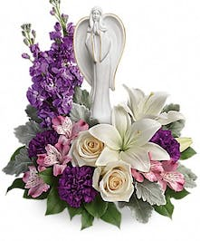 Purple and white flowers surrounding an angel scuplture keepsake.