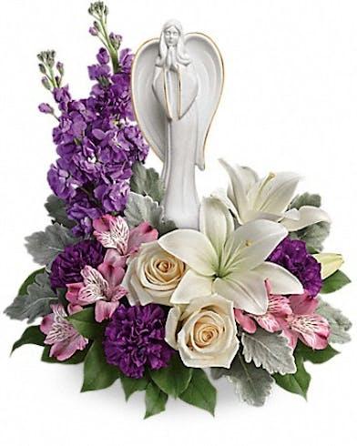 Purple and white flowers surrounding an angel scuplture keepsake.