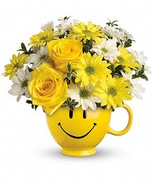 White daisies and yellow roses in a happy face mug.