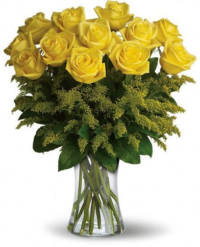 One dozen yellow roses and greenery in a clear glass vase.