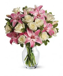One dozen white roses mixed with pink lilies in a clear glass vase.
