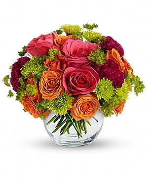 Hot pink, orange and green flowers in a clear glass vase.