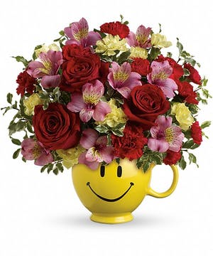 Red and pink flowers in a yellow smile mug.