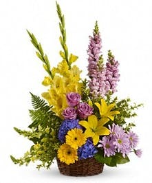 Sympathy basket of bright yellow, lavender and blue flowers.