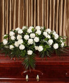Casket spray of white carnations with assorted foliage.