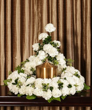 Arrangement of white carnations to surround a memorial urn.