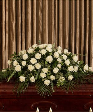 Casket spray of all white roses and greenery.