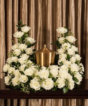 Sympathy display of white roses to surround an urn.
