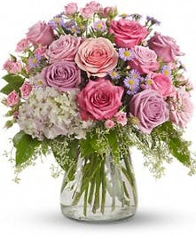 Lavender and pink flowers in a clear glass hurricane vase