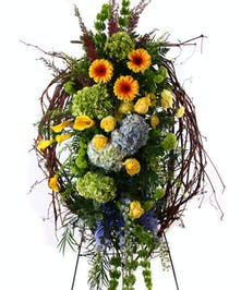 Sympathy spray of hydrangea, calla lilies, gerbera daisies, roses, grapevine and more.