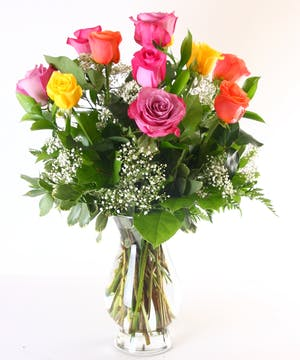 Roses in assorted colors in a glass vase with greenery and baby's breath.
