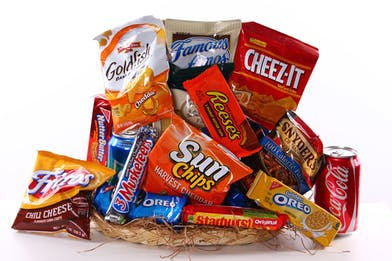 Gift basket filled with candy, soda and chips.