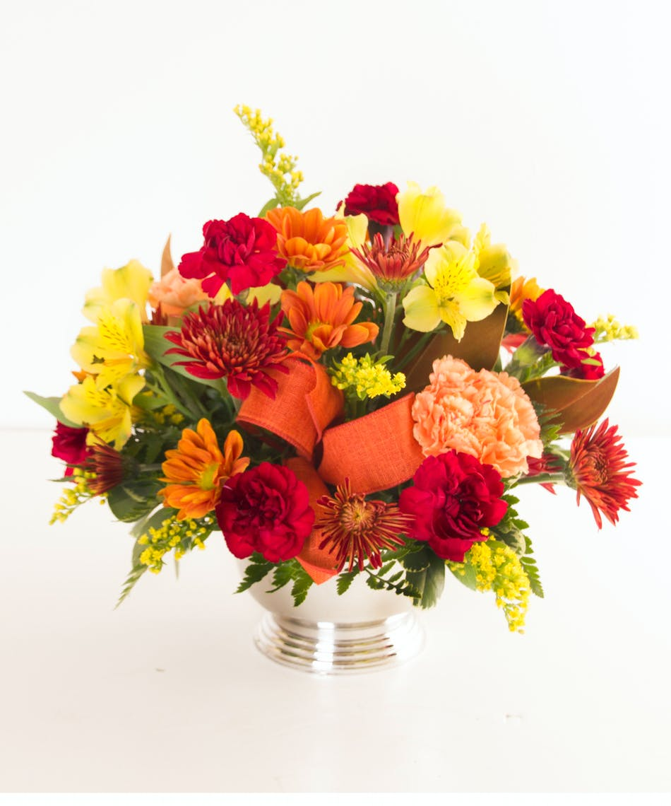 A mix of fresh fall flowers in a silver vase tied with ribbon.