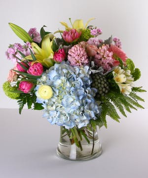 Pastel flower arrangement in a clear glass vase.