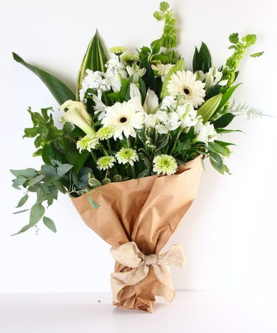 Green and white flowers wrapped in brown paper and finished with a bow.