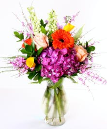 Bright gerbera daisies, roses and calla lilies in a clear glass vase.