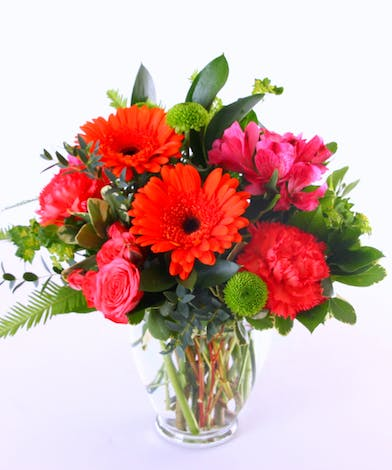 Orange gerberas, carnations and alstroemeria in a clear glass vase.