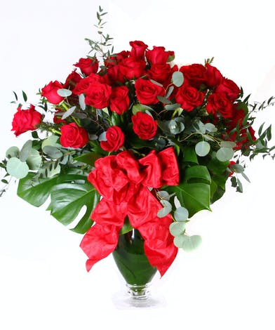 Four dozen roses in a vase with a large bow