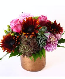 Lovender roses, sunflowers, succulents and dahlias in a copper-look container.