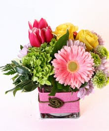 Pink, purple and yellow flowers in a fabric wrapped cube vase.