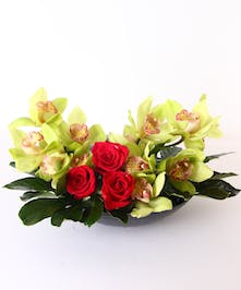 Green cymbidium orchids and red roses in a dish with river rocks.