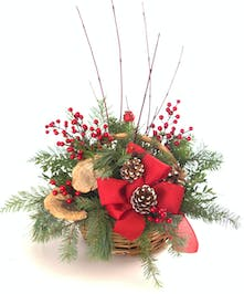 Holiday basket of winter greenery, branches and seasonal trims.