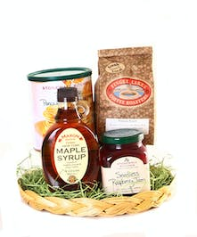 Gift basket filled with maple syrup, pancake mix and jam.