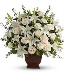 Elegant sympathy bouquet of creme roses, white lilies and more in an urn.