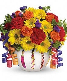 Orange, yellow and red flowers in a birthday keepsake container.