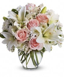 Light pink and white flowers in a clear glass vase.