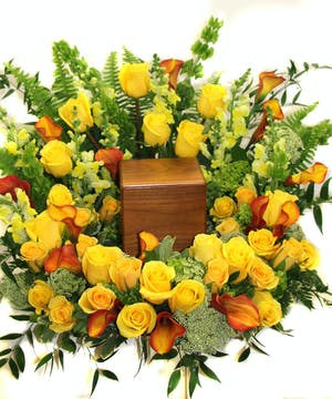 Wreath of yellow roses, calla lilies and assorted greenery to surround an urn or photograph.