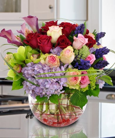 Hydrangea, roses, calla lilies and orchids in a bubble bowl vase.