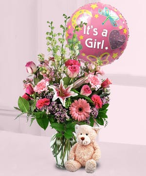 Pink flowers and greenery in a clear glass vase with teddy bear and