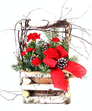Holiday bouquet of mixed winter greenery, red carnations, and more in a birch log basket.